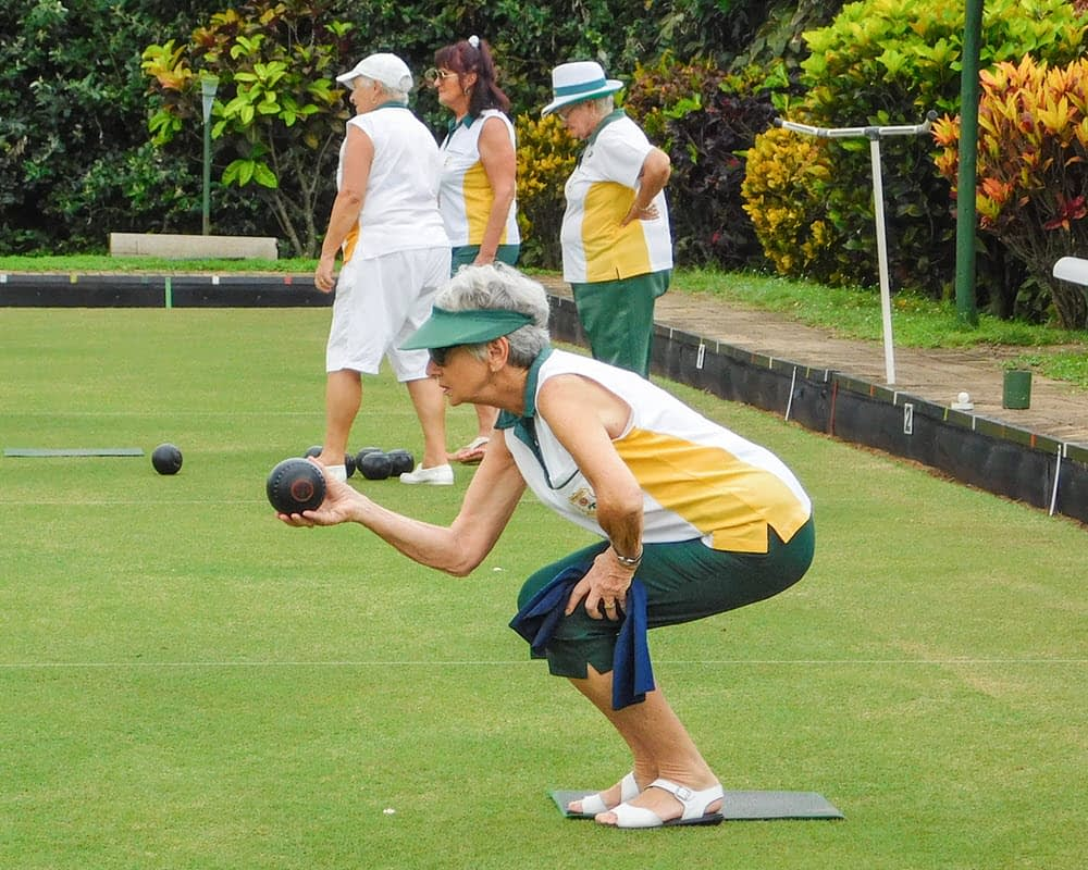 Lady bowler dressed in the club's gold and green colours